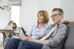 Rodzice ogląda TV na kanapie z dziećmi używa laptop w tle fotografia royalty free
