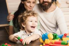 Rodzice oglądają ich syna chwyta budowy robić z bloków fotografia stock