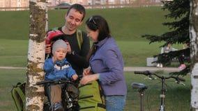 Rodzice ubierają berbecia z rowerowym hełmem w parku Chłopiec siedzi w dziecka siedzeniu przed bicyklem zbiory