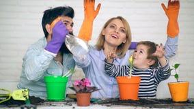 Rodzice uczą chłopiec dlaczego dbać dla kwiatów Rodzinni roślina kwiaty w wiośnie w barwionych garnkach zbiory wideo