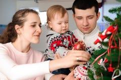 Rodzice z córką ubierają w górę choinki obrazy stock