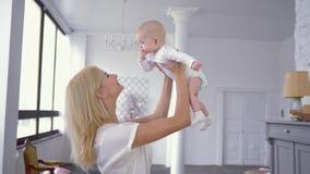 Rodzicielska miłość, szczęśliwi potomstwa matkuje sztuki i podwyżki nad głowa śliczna dziecięca dziewczynka która bitting palce zbiory