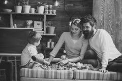 Rodzicielska uwaga Ojcuje, matka i śliczna syn sztuka z konstruktor cegłami Troskliwych rodziców pojęcie Rodzina na ruchliwie Obraz Stock