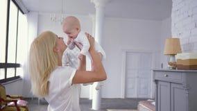 Rodzicielski buziak, potomstwo matki podwyżki nad głowa w zwolnionym tempie słodka nowonarodzona dziewczyna z palcem w usta zbiory wideo