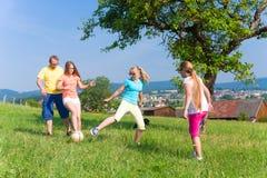 Rodzina bawić się piłkę nożną na łące w lecie Zdjęcia Stock
