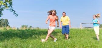 Rodzina bawić się piłkę nożną na łące w lecie Zdjęcie Stock