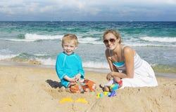 Rodzina bawić się w piasku przy plażą obraz stock