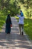 Rodzina chodzi w parku - kobieta w hijab, mężczyzna niesie dziecka na jego ramionach widok z powrotem zdjęcie stock