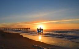 Rodzina cieszy się czas na plaży przy wschodem słońca Obraz Stock