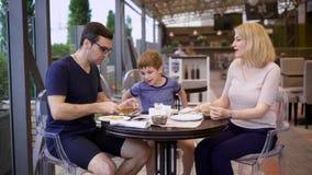 Rodzina cieszy się posiłek wszystko w restauraci wpólnie, śmia się i gawędzi z each inny, zbiory