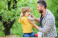 Rodzina cieszy si? domowej roboty posi?ek Ojca syn je jedzenie i zabawę Chłopiec i taty łasowanie Odżywianie dla dzieciaków i dor fotografia stock