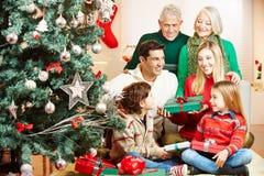 Rodzina daje prezentom przy bożymi narodzeniami zdjęcia stock