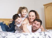 Rodzina, dzieci i domowy pojęcie, - szczęśliwa rodzina z dwa dzieciakami pod koc w domu obrazy royalty free