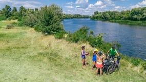 Rodzina jeździć na rowerze outdoors na rowerach, aktywny wychowywa i dzieciaki na bicyklach, widok z lotu ptaka szczęśliwa rodzin zdjęcie stock