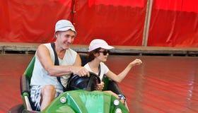 Rodzina jedzie carousel samochód ma zabawę w parku rozrywki obrazy stock