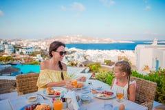 Rodzina ma śniadanie przy plenerową kawiarnią z zadziwiającym widokiem na Mykonos miasteczku Urocza dziewczyna i mama pije świeże Obrazy Stock