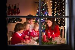 Rodzina ma Bożenarodzeniowego gościa restauracji przy pożarniczym miejscem Obraz Stock
