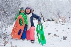 Rodzina ma zabawę z saniem w zima parku Fotografia Royalty Free