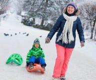Rodzina ma zabawę z saniem w zima parku Zdjęcie Royalty Free