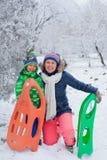 Rodzina ma zabawę z saniem w zima parku Fotografia Stock