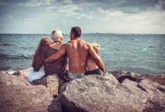 Rodzina na kamiennym wybrzeżu blisko morza Zdjęcia Royalty Free