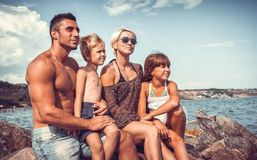 Rodzina na kamiennym wybrzeżu blisko morza Fotografia Royalty Free