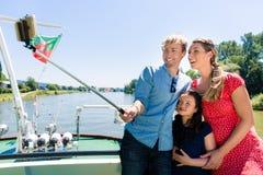Rodzina na rzecznym rejsie z selfie kijem w lecie obraz royalty free