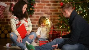 Rodzina na wigilii przy grabą Rodzice I małe dziecko Otwiera Xmas teraźniejszość Dzieci z prezentów pudełkami _ zbiory