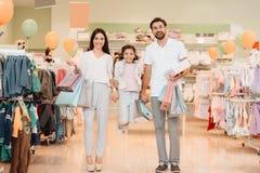 Rodzina, ojciec, matka i córka, jesteśmy w ubrania sklepie centrum handlowe Dziewczyna skacze zdjęcie stock
