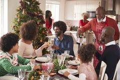 Rodzina opowiada szkła i podnosi przy obiadowym stołem podczas wielo- pokolenia, mieszający biegowy rodzinny Bożenarodzeniowy świ zdjęcia stock