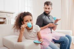Rodzina pije herbaty podczas gdy mieć herbacianego przyjęcia w domu Obraz Royalty Free