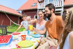 Rodzina pije kawę i je torta przód dom Zdjęcia Royalty Free