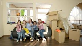 Rodzina pokazuje aprobaty, pudełka zbiory wideo