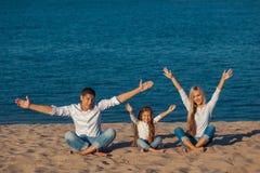 Rodzina przy plażą Lotosowa postura ręce do góry Zdjęcie Stock