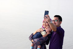 Rodzina przy plażą robi jaźń portretowi z telefonem komórkowym Zdjęcie Stock