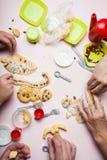 Rodzina przygotowywa Bożenarodzeniowych ciastka w postaci bałwanów i choinki z wysuszonymi jagodami zdjęcia stock