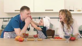 Rodzina przygotowywa sałatki w kuchni Syn karmi ojciec i matka truskawki zbiory