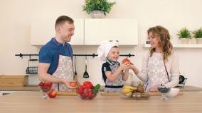 Rodzina przygotowywa sałatki w kuchni Tata i mama rzucamy jabłka up Syn jest uśmiechnięty zbiory