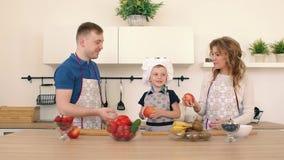 Rodzina przygotowywa sałatki w kuchni Tata i mama rzucamy jabłka up Syn jest uśmiechnięty zbiory wideo