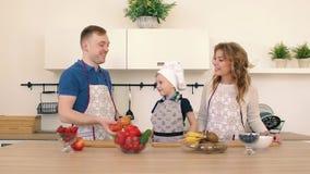 Rodzina przygotowywa sałatki w kuchni Tata rzuca jabłka up Syn i jego matka jesteśmy uśmiechnięci zbiory