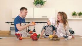 Rodzina przygotowywa sałatki w kuchni Tata rzuca jabłka up Syn i jego matka jesteśmy uśmiechnięci zdjęcie wideo
