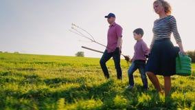 Rodzina rolnicy z małym synem iść wpólnie zasadzać drzewa Znosi jabłoni rozsady, łopatę i podlewanie ochraniacza, zbiory wideo