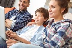 Rodzina siedzi na kanapie w żywym pokoju wpólnie ogląda film na laptopie rozochoconym w górę w domu fotografia royalty free