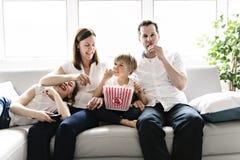 Rodzina składająca się z czterech osób ma zabawę na kanapie ogląda film z popkornem w domu obrazy royalty free