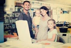 Rodzina składająca się z czterech osób robi zakupy pralkę w handlu detalicznym obraz stock