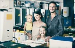 Rodzina składająca się z czterech osób stoi blisko elektronika w gospodarstwie domowym zdjęcie stock