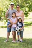 Rodzina składająca się z czterech osób trzyma kij bejsbolowego i piłkę w parku Fotografia Royalty Free