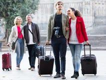 Rodzina składająca się z czterech osób z bagażnikami chodzi przez miasto ulicy obraz royalty free