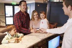 Rodzina Sprawdza Wewnątrz Przy Hotelowym Recepcyjnym biurkiem Zdjęcia Stock