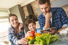 Rodzina stoi w kuchnia syna i matki łasowania vegetbles wpólnie w domu podczas gdy ojciec pracuje na cyfrowej pastylce obraz royalty free